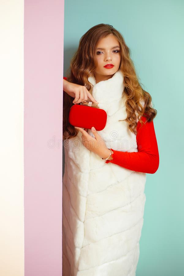 Perfect for carrying her essentials with ease. Fashion girl wear glamorous fur vest with mini red bag. Young woman in royalty free stock images