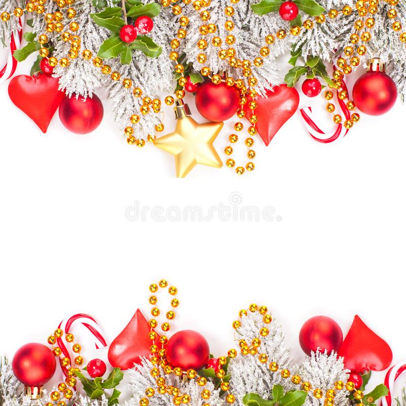 Perfect Christmas border composition with red holly berries, glass baubles, golden garland and snowy Xmas tree branch isolated. On white background. Bright Xmas royalty free stock photos