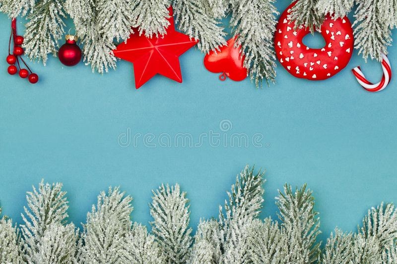 Perfect Christmas composition border. Blue background with red holly berries, candy and green fir branch.  royalty free stock photos
