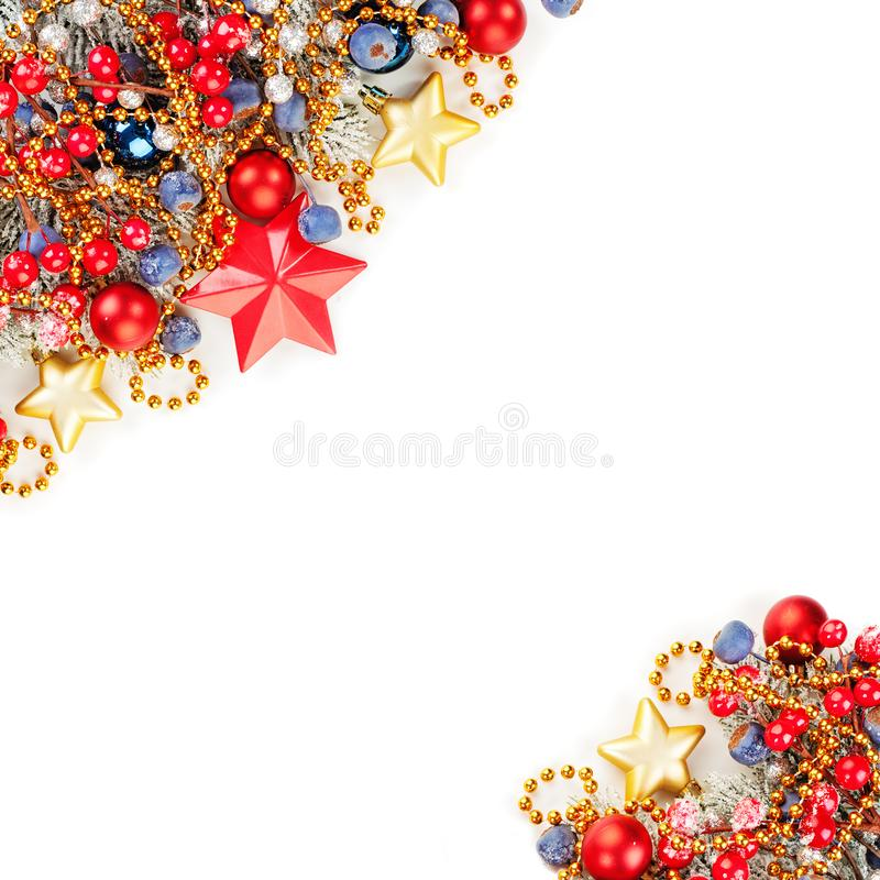 Perfect Christmas composition card. Colorful border background with green Xmas tree twig, holly berries, red and blue baubles royalty free stock image