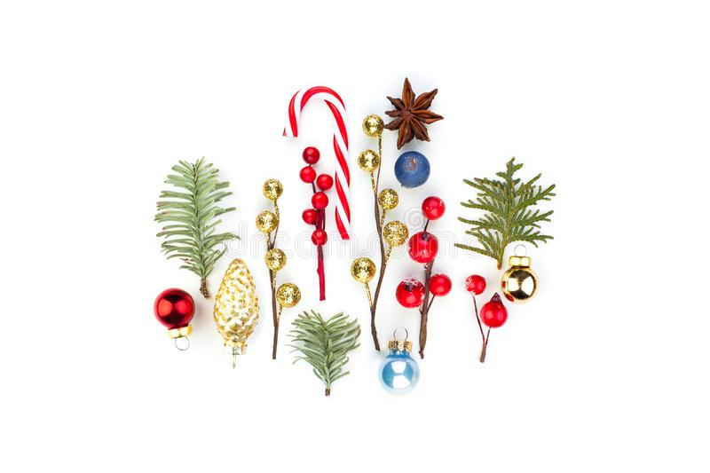 Perfect Christmas composition. Red baubles, snowy winter holly berries, lollipop and natural green fir branch on white background royalty free stock image