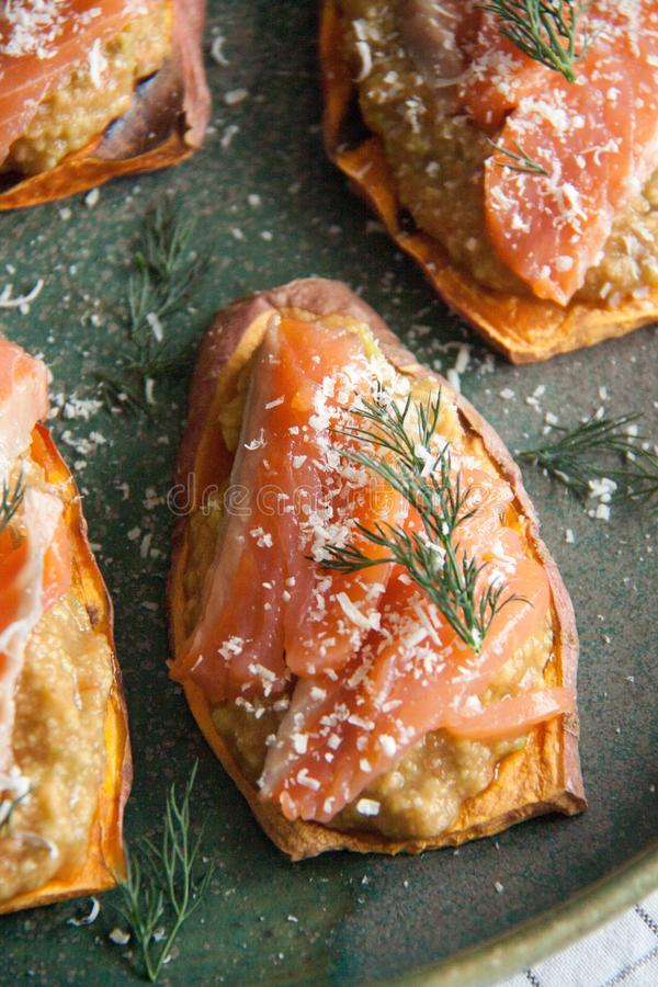 Baked sweet potato with avocado pasta and salmon. Perfect cozy and delicious breakfast: Baked sweet potato with avocado pasta and salmon, cheese and dill on a royalty free stock images