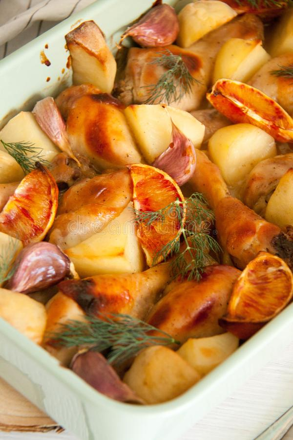 Oven baked chicken legs with potato and red oranges. Perfect cozy and delicious dessert: Oven baked chicken legs with potato and red oranges in a green baking stock image