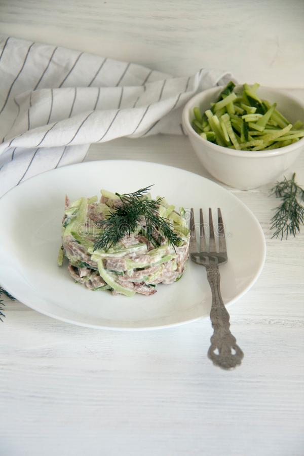 Beef tongue and fresh cucumber salad. Perfect cozy and delicious lunch: beef tongue and fresh cucumber salad with mayo and horseradish on a white plate royalty free stock image