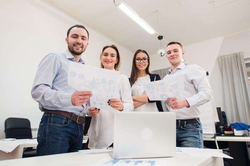 Perfect creatief team Groep van vier vrolijke jongeren die camera met glimlach bekijken terwijl binnen het leunen aan de lijst royalty-vrije stock afbeeldingen