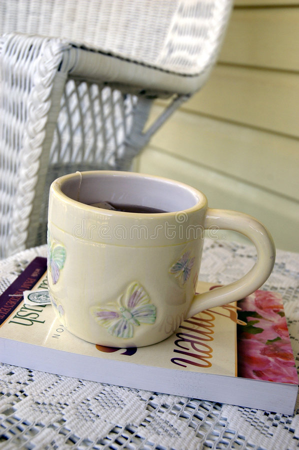 The Perfect Cup Of Tea. All about the feminine; soft yellow, butterflys on the cup, and a book with roses on the cover stock image