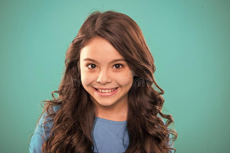 Perfect curling hair. Kid girl long healthy shiny hair. Kid happy cute face with adorable curly hairstyle stand over stock photography
