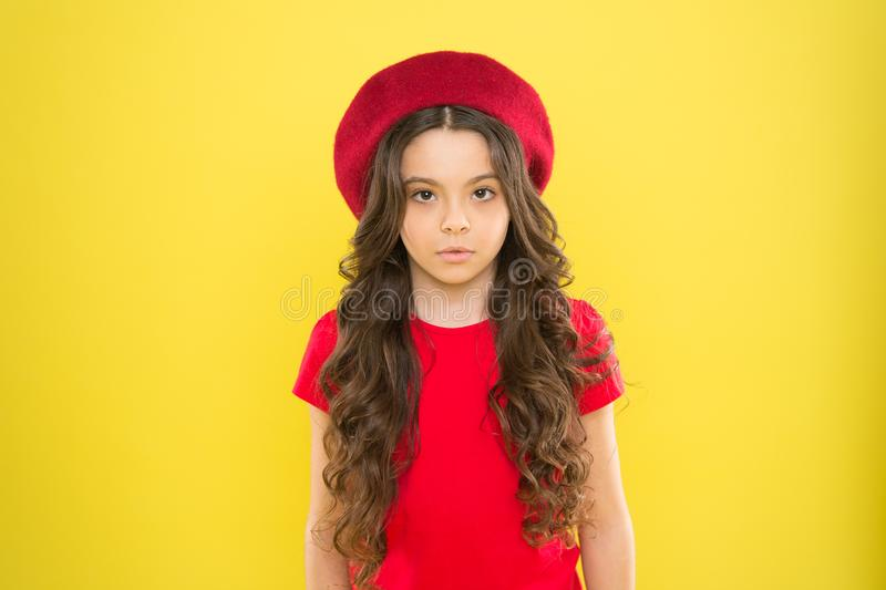Perfect curls. Kid girl long healthy shiny hair. Kid cute face with adorable curly hairstyle wear beret hat. Little stock image