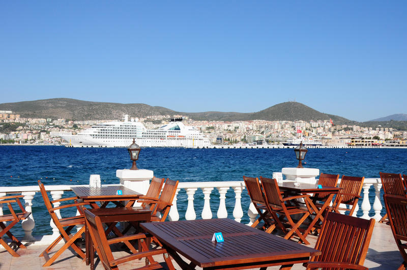 Perfect dinner spot on a terrace in Kusadasi. Turkey with a beautiful cruise ship in the background royalty free stock images