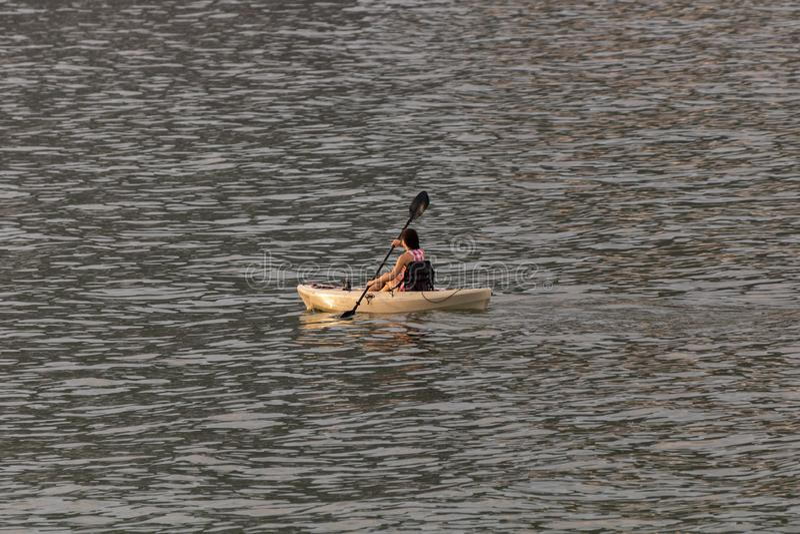 Perfect dzień dla kayaking Piękna młoda kobieta paddling podczas gdy siedzący w kajaku obrazy stock