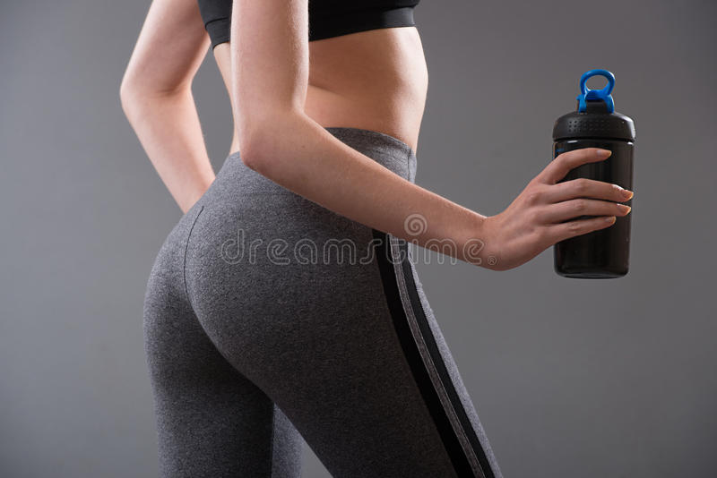 Perfect female body shape after fitness and sport protein food drinks. Perfect female body shape after fitness and sport protein food drinks royalty free stock photos