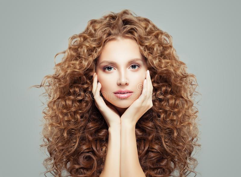 Perfect female face. Attractive girl with long curly hair. Haircare and cosmetology concept stock image