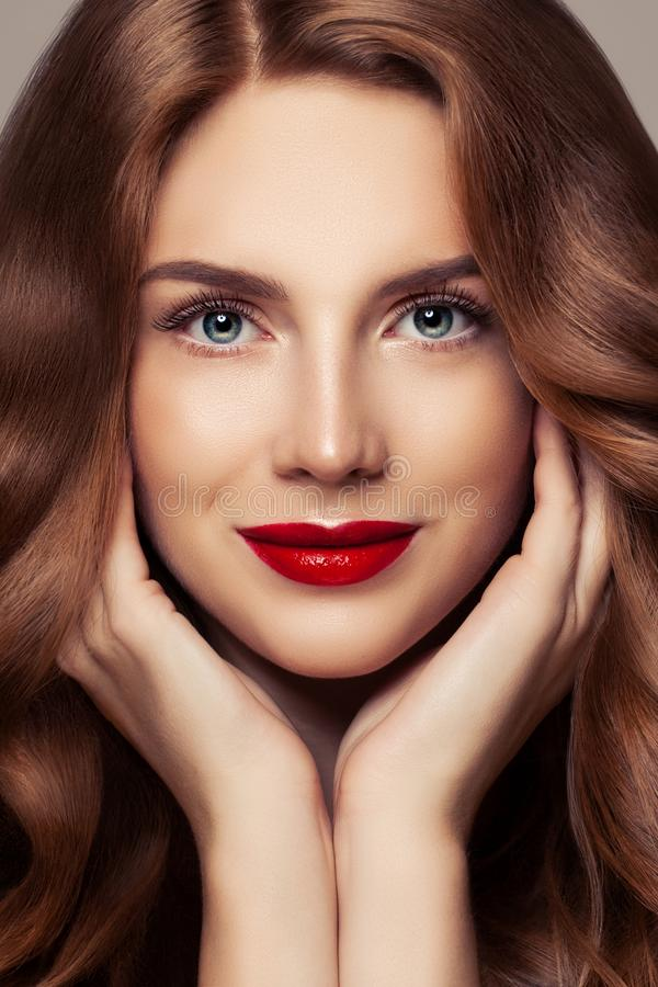 Perfect female face closeup portrait. Pretty woman with curly shiny hair and red lips makeup stock photo