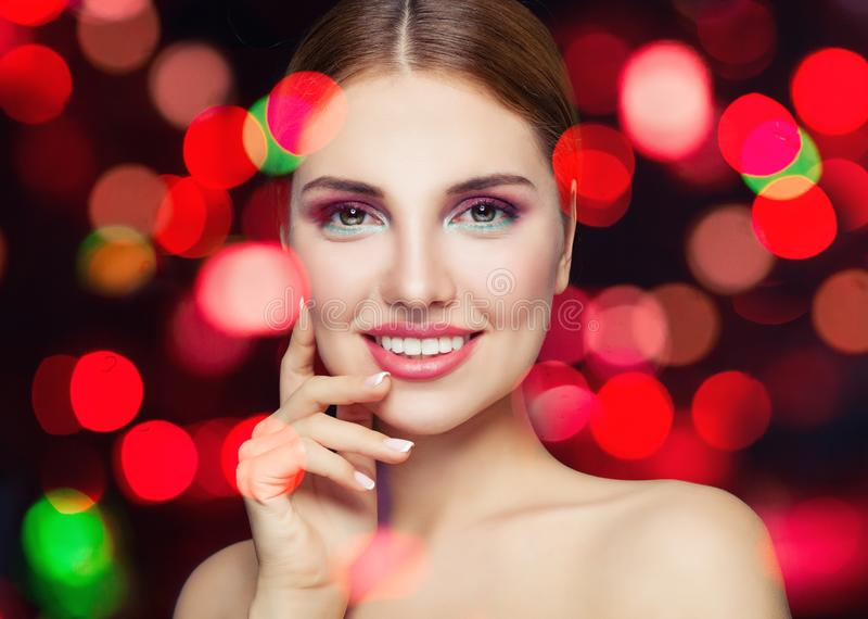 Perfect female face closeup. Young smiling woman with makeup on party glitter background. royalty free stock images