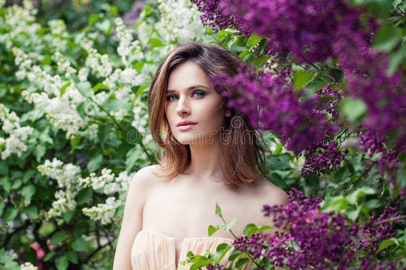 Perfect female face in lilac flowers garden. Pretty woman on floral background stock photos