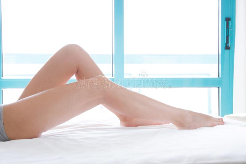 Perfect female legs on bed with bent knees side view. Cropped image of erotically lying on bed woman in bedroom. Copy space, royalty free stock photo
