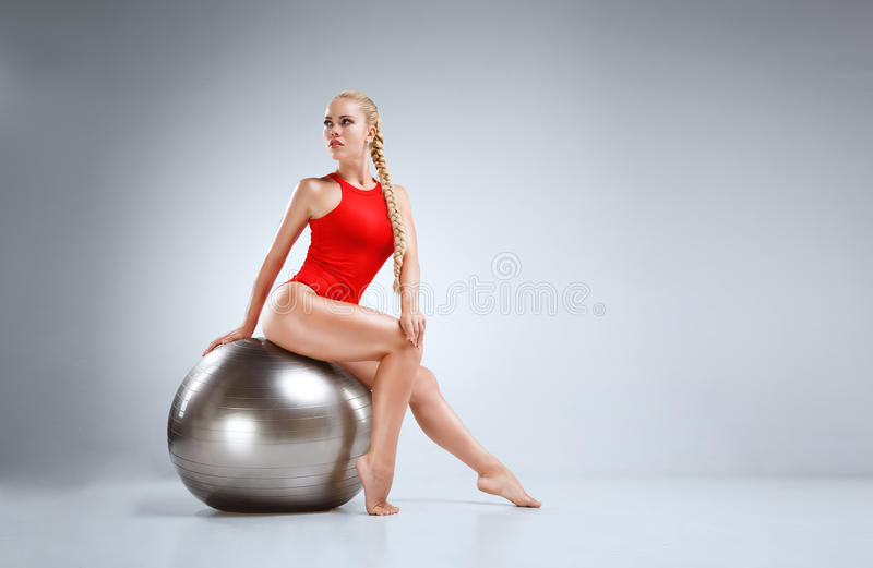 Perfect fitness motivation. High fashion portrait of a slim and beautiful fitness model with blonde hair posing in a red bodysuit on a grey background royalty free stock image