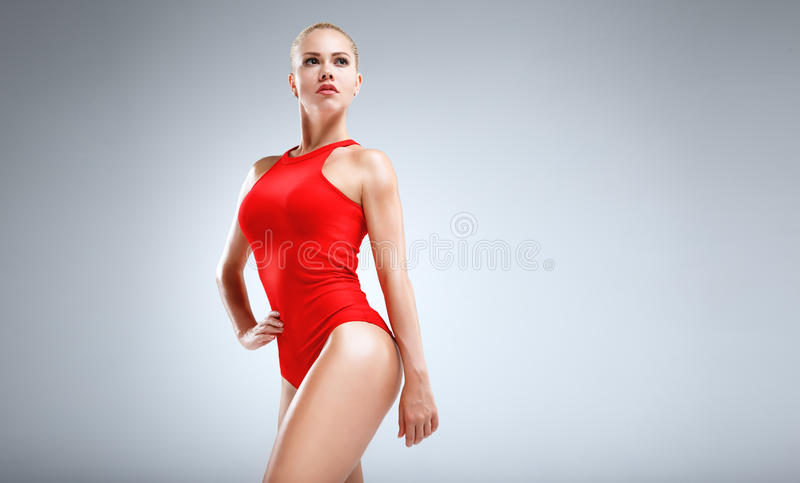 Perfect fitness motivation. High fashion portrait of a slim and beautiful fitness model with blonde hair posing in a red bodysuit on a grey background stock image