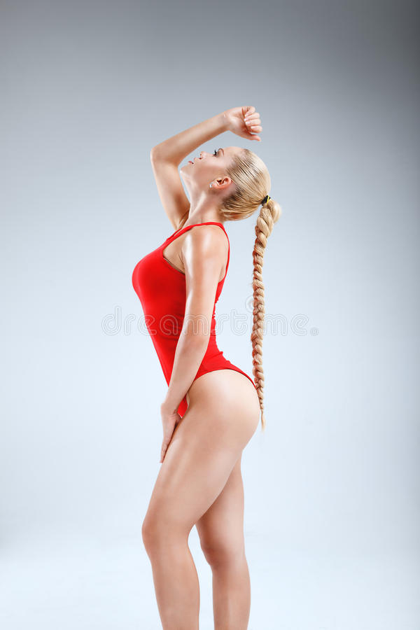 Perfect fitness motivation. High fashion portrait of a slim and beautiful fitness model with blonde hair posing in a red bodysuit on a grey background stock photos