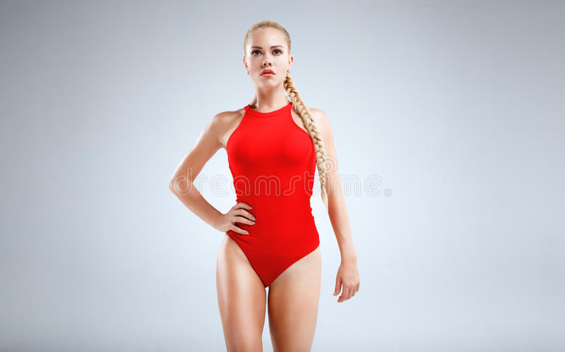 Perfect fitness motivation. High fashion portrait of a slim and beautiful fitness model with blonde hair posing in a red bodysuit on a grey background royalty free stock photography