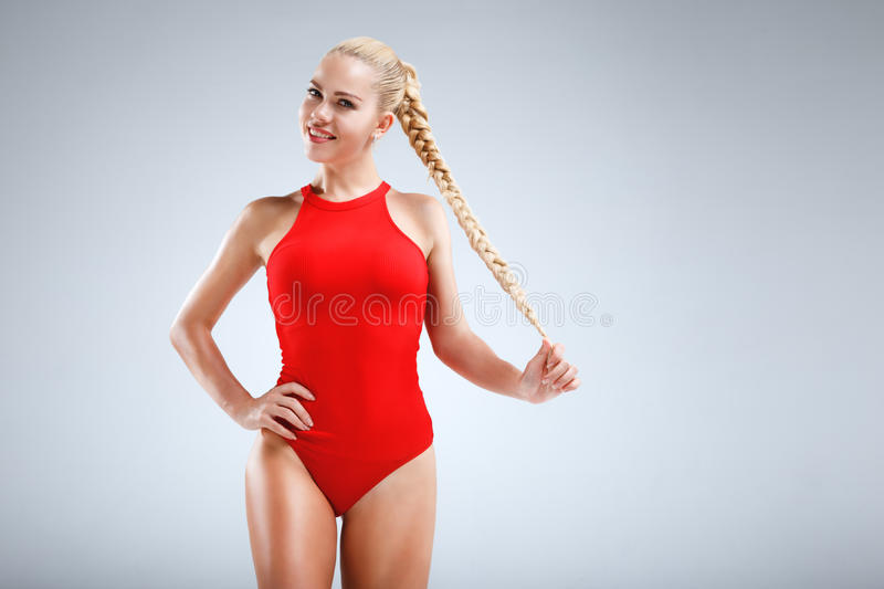 Perfect fitness motivation. High fashion portrait of a slim and beautiful fitness model with blonde hair posing in a red bodysuit on a grey background stock images