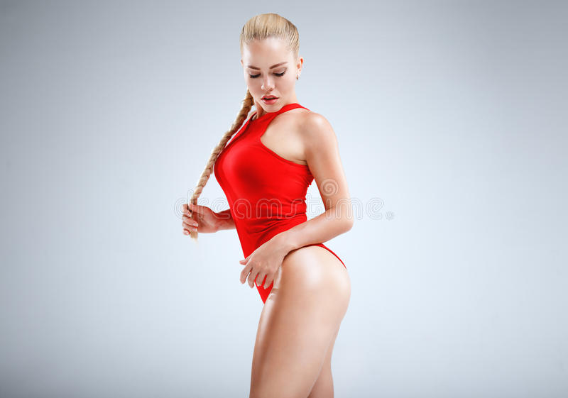 Perfect fitness motivation. High fashion portrait of a slim and beautiful fitness model with blonde hair posing in a red bodysuit on a grey background stock photography