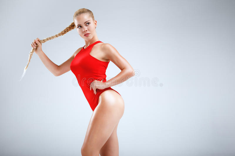 Perfect fitness motivation. High fashion portrait of a slim and beautiful fitness model with blonde hair posing in a red bodysuit on a grey background stock photo