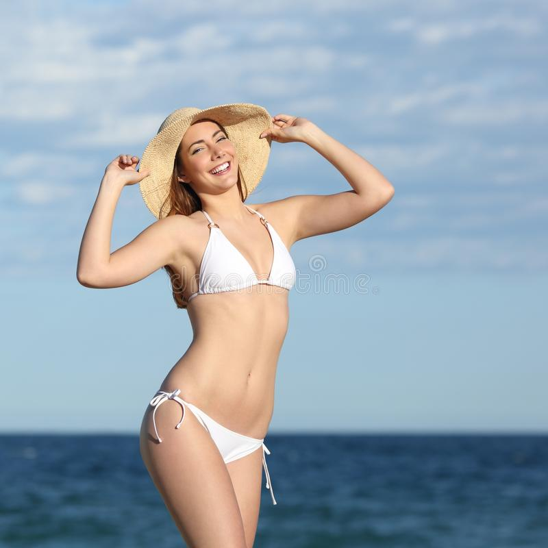 Perfect fitness woman body posing on the beach. With the sea in the background royalty free stock images