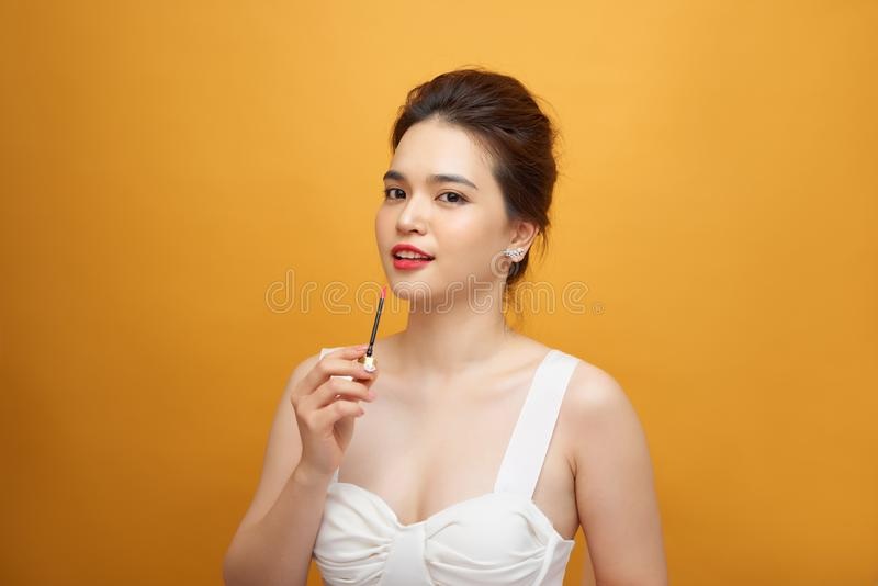 Perfect girl holding lipstick on yellow background, close up portrait stock photography