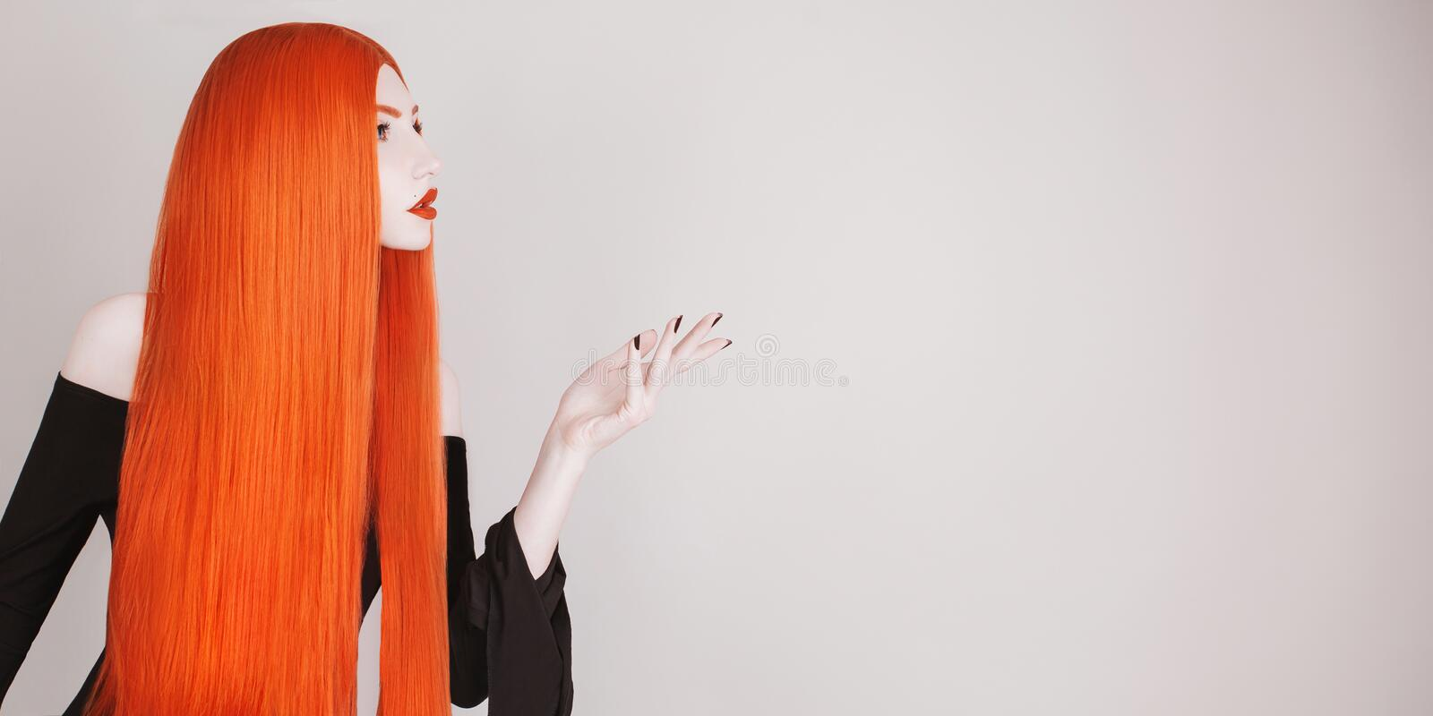 Perfect halloween attire. Gothic redhead woman with perfect straight hair in black dress advertise product. Redhead girl with red. Lips. Gothic look. Hair stock image