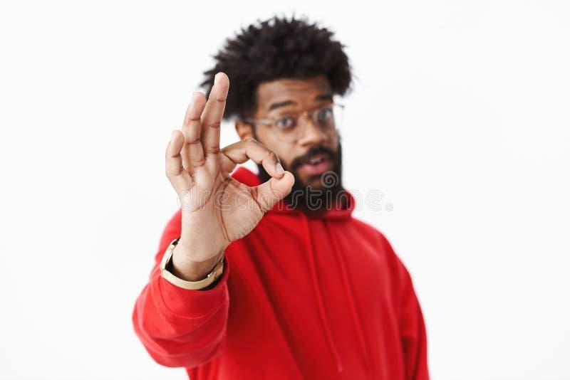 perfect Het vage schot van Afrikaanse Amerikaanse gebaarde kerel in het rode hoodie trekken dient nadruk naar camera in die o.k.  stock foto