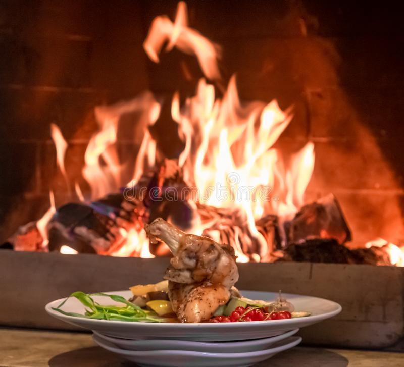 Exquisitely served chicken with vegetables on the background of the fire. stock photos