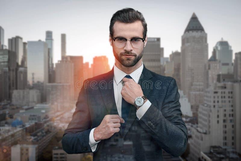 Perfect kijk! Zekere bedrijfsdeskundige die in glazen stropdas aanpassen terwijl status in openlucht met cityscape op stock afbeeldingen