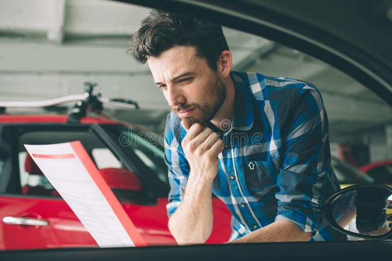 Perfect lines. The young dark-haired bearded man examining car at the dealership and making his choice. Horizontal royalty free stock photos