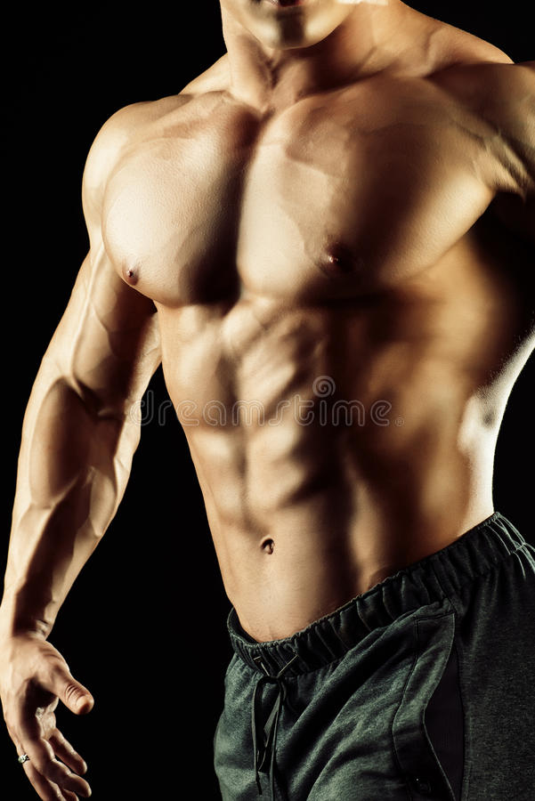 Perfect male body. Close-up shot of a handsome muscular bodybuilder posing over black background royalty free stock photo
