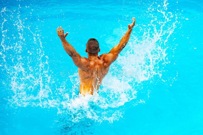 Perfect male Torso on blue water background. Vacation at Paradise. Vacation. Luxury Travel Expert. Young man Swimming royalty free stock image