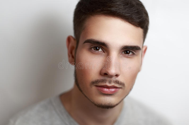 Perfect man. Young handsome pretty brown-haired man boy model actor. Natural makeup, expressive eyebrows, brown eyes, perfect face nose lips. Stylish, chic royalty free stock photography
