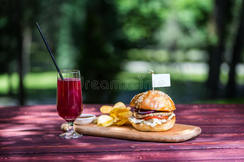 The perfect meat burger with crisps and fresh cold lemonade. On the cutting board, and green summer background. stock photo