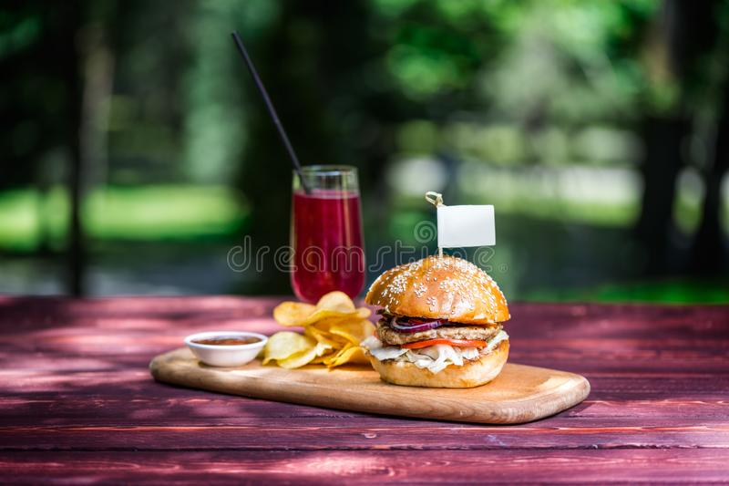 The perfect meat burger with crisps and fresh cold lemonade. On the cutting board, and green summer background. royalty free stock photo
