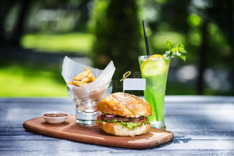 Perfect meat burger with french fries and fresh cold lemonade. On the cutting board, and green summer background. royalty free stock photos