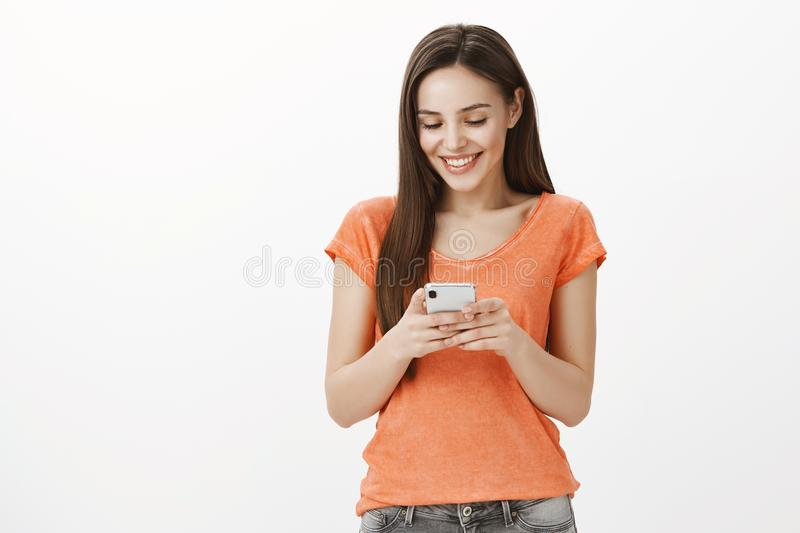 Perfect message from boyfriend. Studio shot of satisfied beautiful dark-haired caucasian woman in orange outfit, holding stock photography
