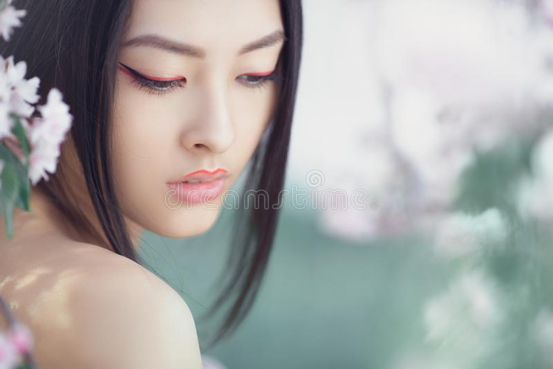 Portrait of a beautiful fantasy asian girl outdoors against natural spring flower background. Perfect model with creative vivid makeup and pink lipstick on lips royalty free stock photography