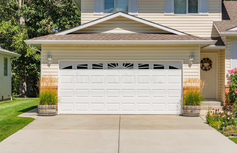 A perfect neighbourhood. Family house with wide garage door and concrete driveway in front royalty free stock photography