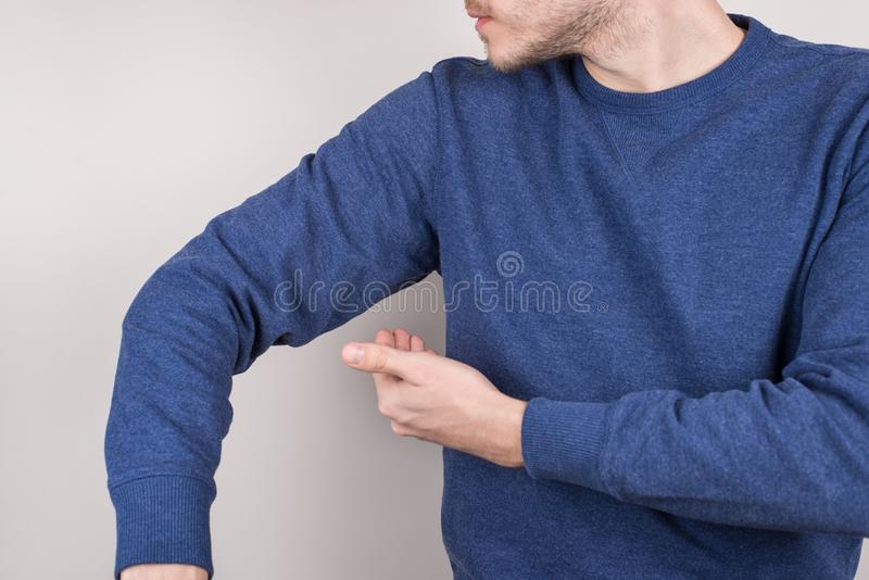 Perfect nice smell reliable deodorant concept. Cropped closeup photo of satisfied guy checking smell under arm  grey royalty free stock photo