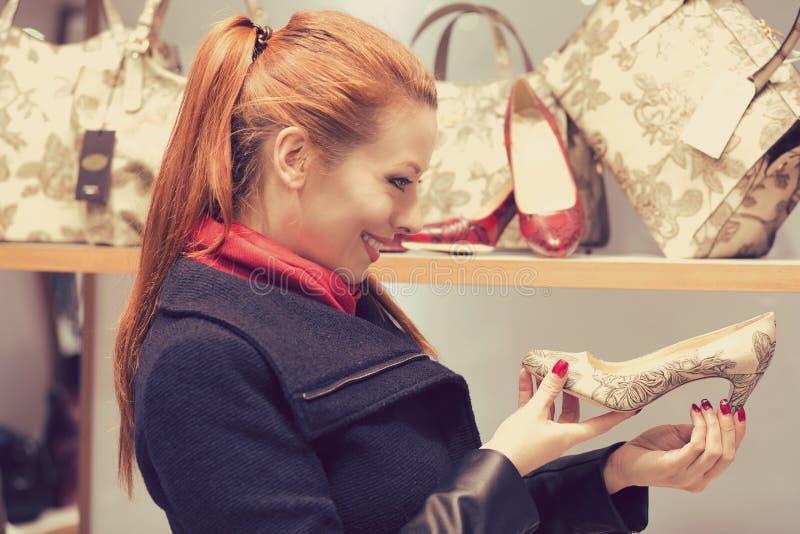 Perfect paar! Vrouw die hoge hielschoenen bekijken terwijl het winkelen in warenhuis stock foto