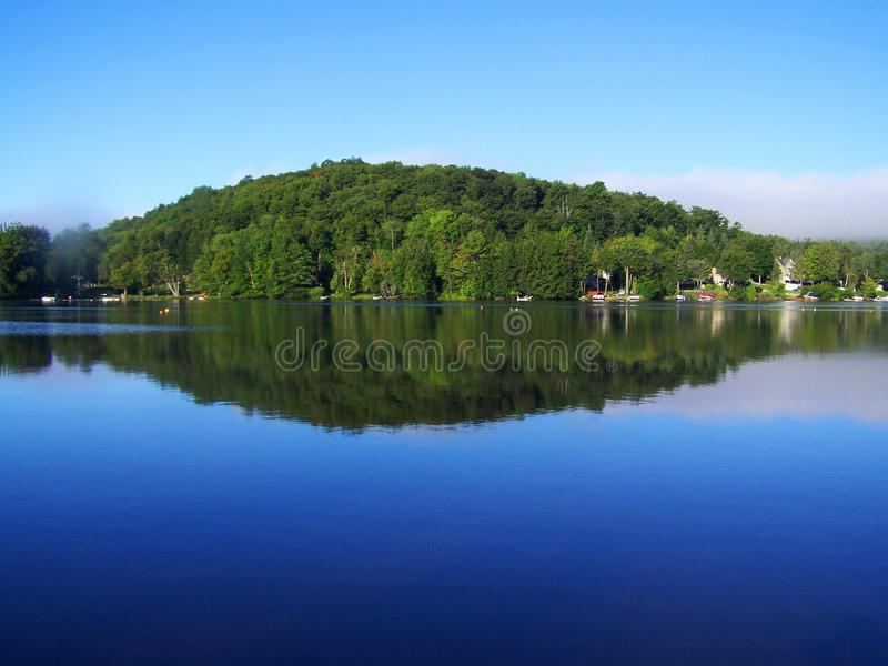 Perfect picture on a bright day and mirror water. Perfect picture of a blue sky, calm water reflecting the sky and the trees stock images