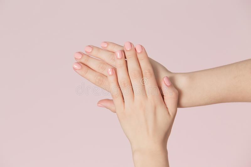 Perfect pink manicure on nails. Beautiful woman hand with clean skin over pink backdrop. stock photos