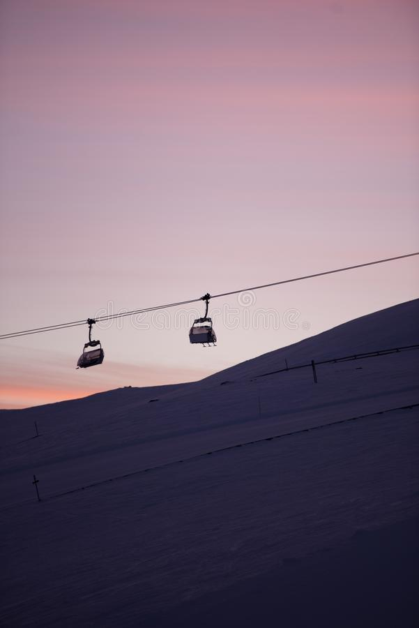 Sunset in skiing resort. Beautiful pink sky. Winter holiday in the mountains. royalty free stock photo