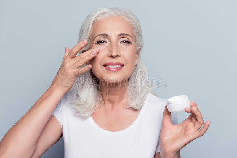 Perfect, pretty, woman applying eye cream, holding jar of cosmetic product looking at camera over gray background royalty free stock image