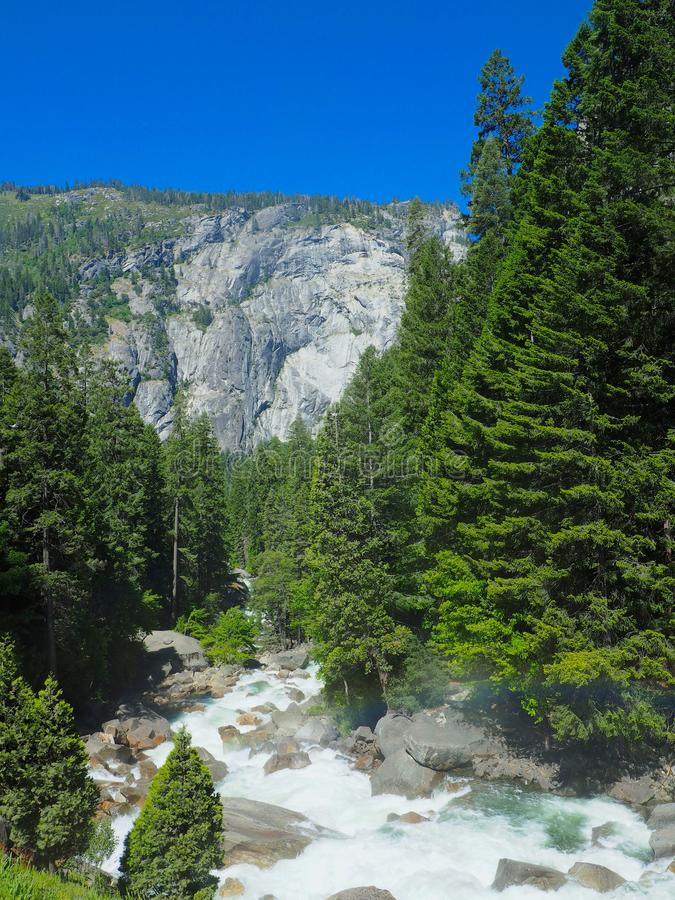 Perfect Rainbow over a Babbling Brook in Yosemite National Park. A perfect arc rainbow over a babbling brook with whitewater in Yosemite National Park in stock image